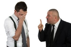 Businessman screaming and fighting at a young colleague