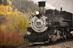 An historic railraod train climbs the Rocky Mountains in autumn